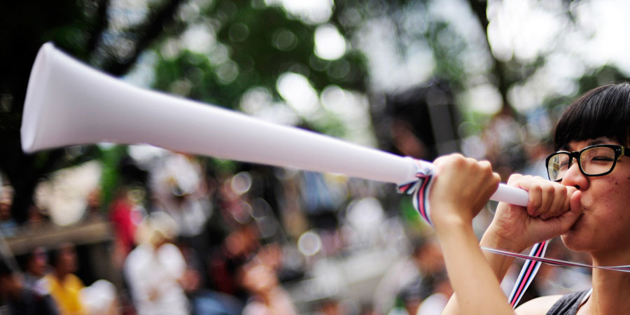 Asian woman sounding a white vuvuzela on a blurred crowd background