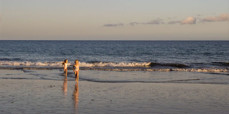 Two young girls in white sleeveless shirts running on the beach toward the photographer.