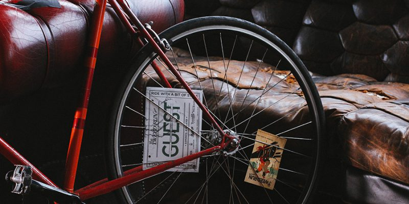 unsplash photo of a bicycle wheel and a worn, wrinkled sofa