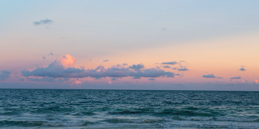 sunrise or sunset photo of pink-hued clouds and choppy sea